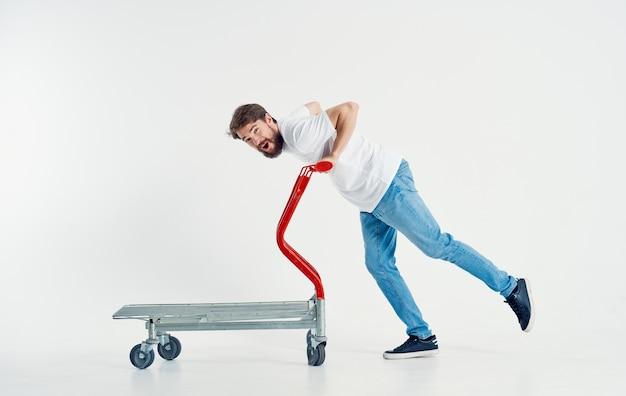 Un uomo trasporta un carrello del carico di lato su uno sfondo chiaro in piena crescita