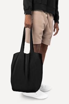 Uomo con borsa nera in studio fotografico