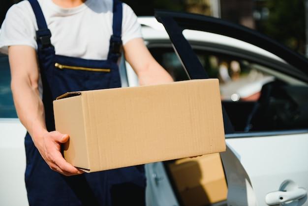 Un uomo che trasporta un pacco dall'auto di consegna - concetto di servizio di corriere