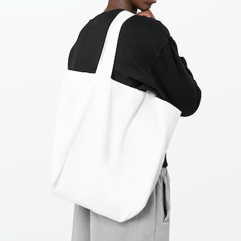 Uomo che porta una borsa della spesa riutilizzabile bianca in studio