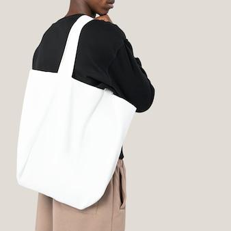 Uomo con borsa bianca in studio fotografico
