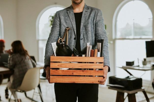 Uomo che porta una scatola di legno in ufficio