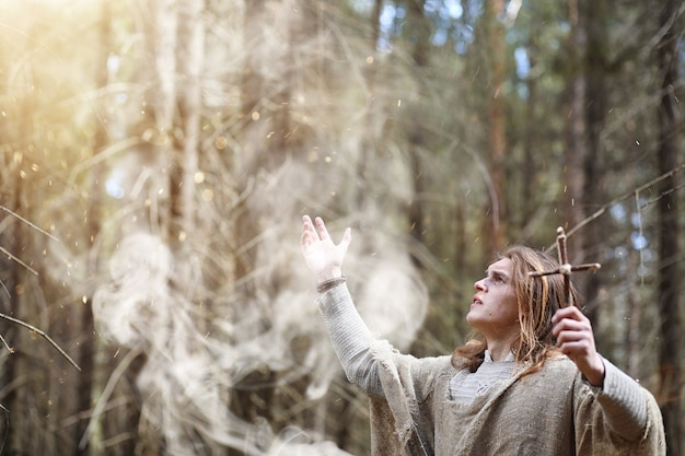 Un uomo in tonaca trascorre un rituale in una foresta oscura con una sfera di cristallo e un libro