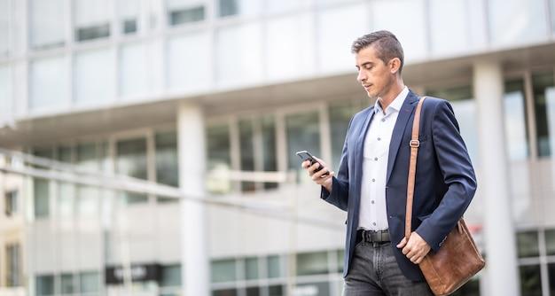 L'uomo in abbigliamento casual controlla il suo telefono camminando all'aperto in un ambiente di edifici per uffici.