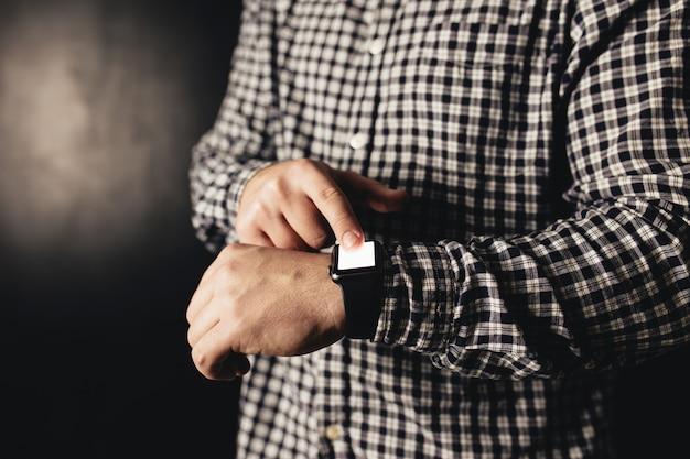 Uomo in abiti casual fa clic su orologi a mano, bracciale, sfondo sfocato nero. foto di alta qualità