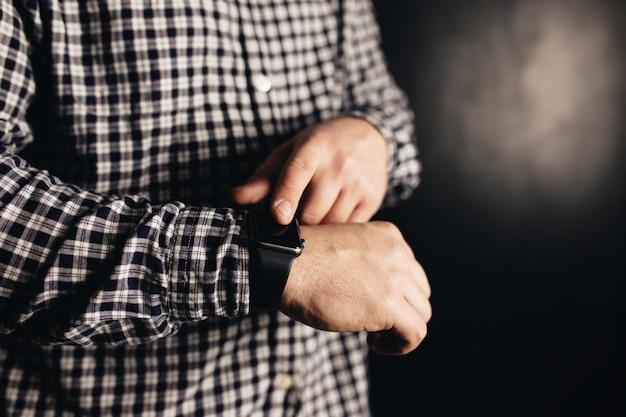 Uomo in abiti casual fa clic su orologi a mano, bracciale, sfondo sfocato nero