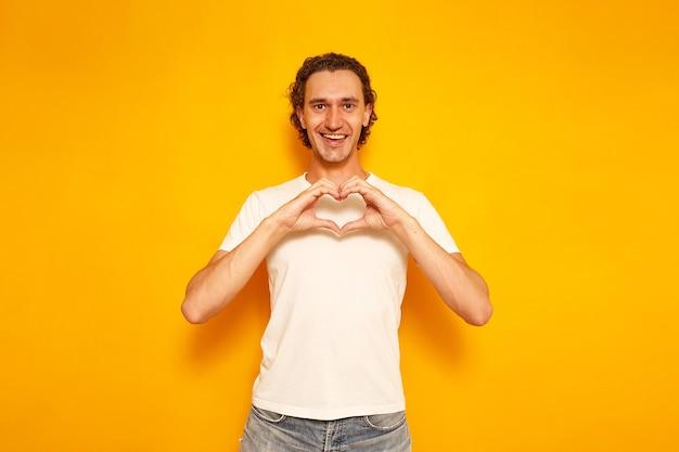 Un uomo in abiti casual incrociò le mani a forma di cuore isolato su uno sfondo giallo