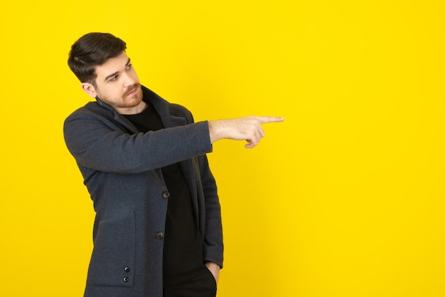 Uomo in abiti casual che punta il dito lontano.