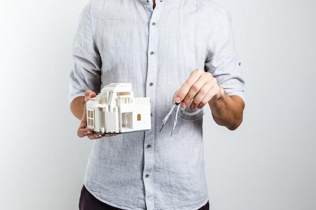 Uomo in abiti casual in posa isolato su priorità bassa bianca della parete. tenendo per mano casa e mazzo di chiavi