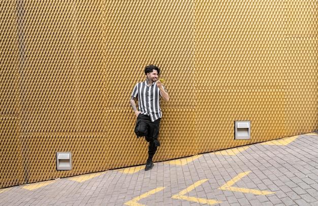 Uomo in abiti casual, su un muro giallo