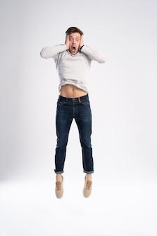 Uomo in maglietta casual e jeans saltando isolato su sfondo bianco.