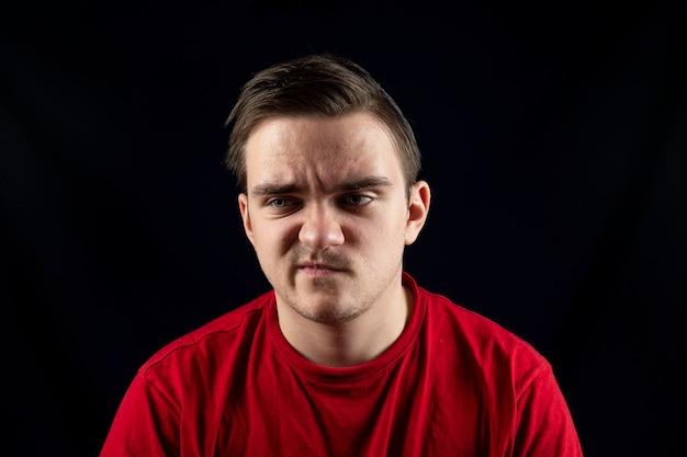 Uomo in maglietta casual in piedi indignato e pensieroso isolato