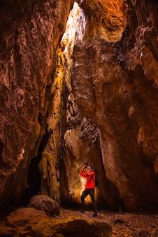 Uomo in grotta, esploratore fotografo esploratore con raggio di luce nella grotta