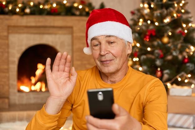 Uomo che celebra il natale a casa a causa dell'epidemia di coronavirus, tiene in mano lo smart phone e saluta qualcuno, agitando la mano, indossa una camicia gialla e un cappello rosso festivo, posa in soggiorno con decorazioni.