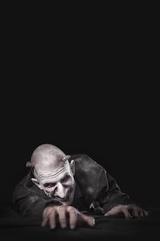 Uomo caratterizzato come uno zombi che striscia sul pavimento. sfondo nero.