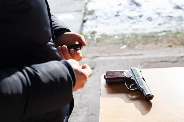Un uomo carica una pistola con proiettili per strada
