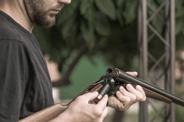 Uomo che carica il primo piano del fucile da caccia a doppia canna