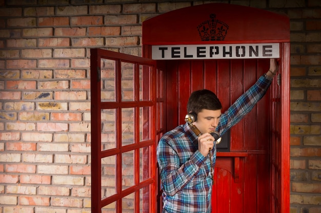 Uomo in chat all'interno di una cabina telefonica britannica rossa appoggiata alla porta aperta ascoltando la conversazione