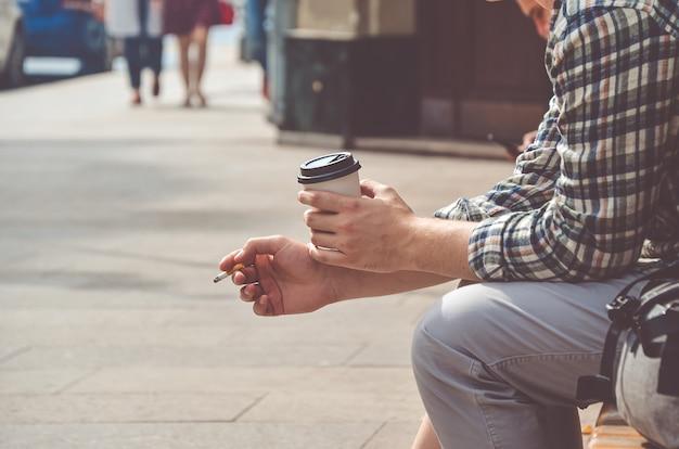 Un uomo con una camicia a quadri è seduto in strada e tiene in mano una tazza di caffè e una sigaretta di cartone. immagine tonica con soft focus.