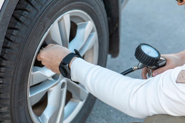 Uomo che controlla la pressione dei pneumatici dell'auto viaggio in auto viaggio su strada
