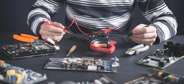 Uomo che controlla la scheda madre del computer con un multimetro.