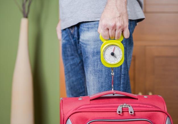 Uomo che controlla il peso del bagaglio a mano utilizzando un equilibrio stadera dalle restrizioni delle compagnie aeree low cost
