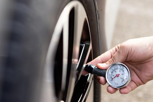Uomo che controlla la gomma della sua auto con il manometro dei pneumatici