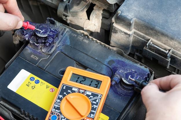 L'uomo controlla la batteria dell'auto utilizzando un multimetro digitale con misurazione della gamma di tensione