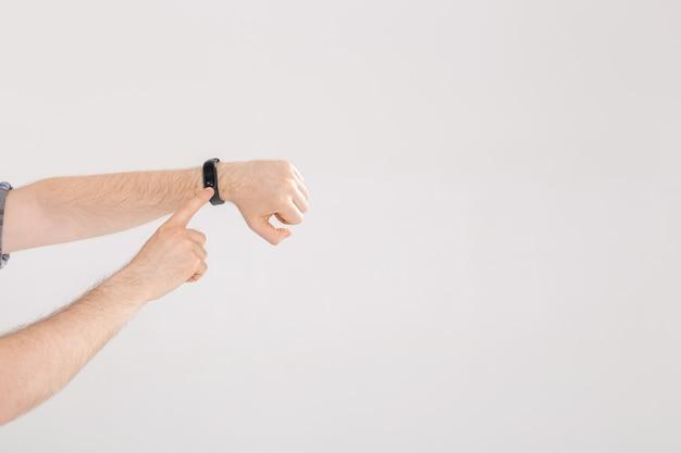 L'uomo controlla il polso sul braccialetto fitness o sul contapassi del tracker di attività sul polso