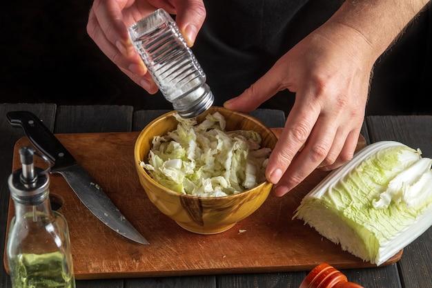 L'uomo chef prepara insalata di napa coleslaw. l'idea di fare una colazione o una cena dietetica