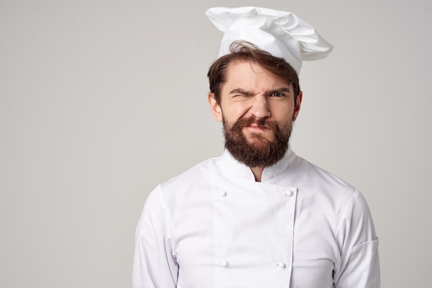 L'uniforme dello chef dell'uomo cucina le emozioni sullo sfondo isolato