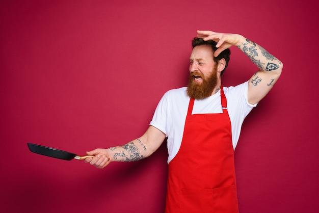 L'uomo chef con la padella in mano si comporta come uno stregone