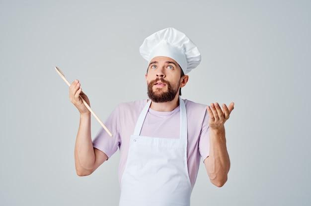 Un uomo in uniforme da chef con la barba che serve un professionista del ristorante