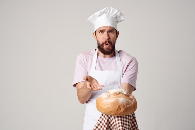 L'uomo in uniforme da chef lavora cucinando il servizio di cottura al forno
