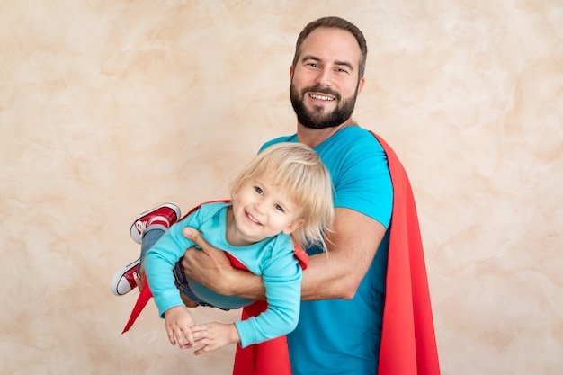 Uomo e bambino super eroe a casa. padre e figlio del supereroe che si divertono insieme.