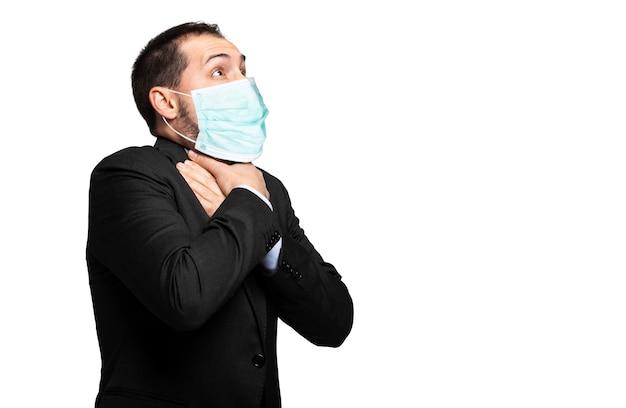 Uomo che soffoca a causa della mancanza di aria isolata su bianco e indossa una maschera, concetto di coronavirus