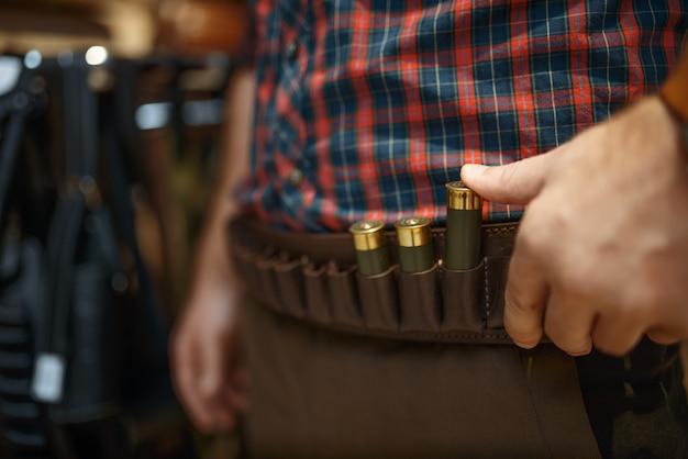 Uomo che sceglie cintura di munizioni e uniforme per la caccia nel negozio di armi.