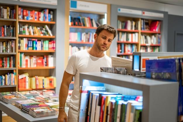 Uomo che sceglie libri in negozio