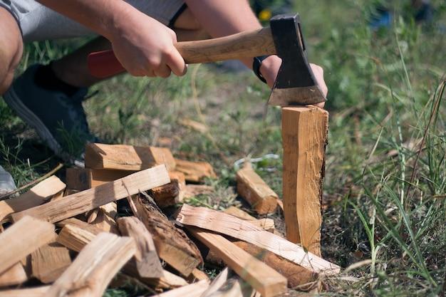 Uomo che taglia la legna con un'ascia per strada