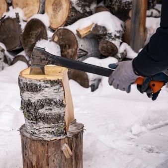 Un uomo taglia zeppe di betulla con un'ascia in inverno