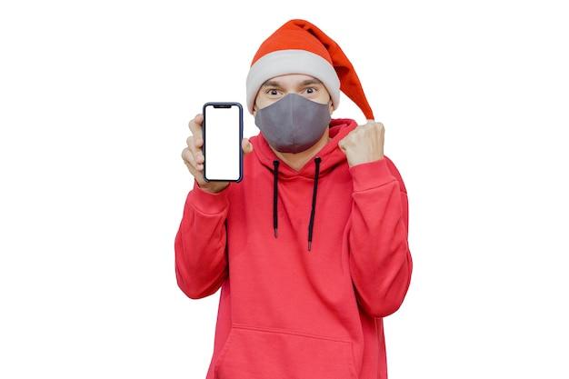 Uomo in cappello di natale con un telefono cellulare e una maschera come simbolo della celebrazione del natale 2020 in tempi di pandemia.