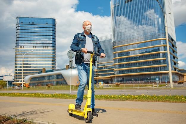 Un uomo in una strada cittadina su uno scooter elettrico con una maschera protettiva per proteggere il coronavirus.