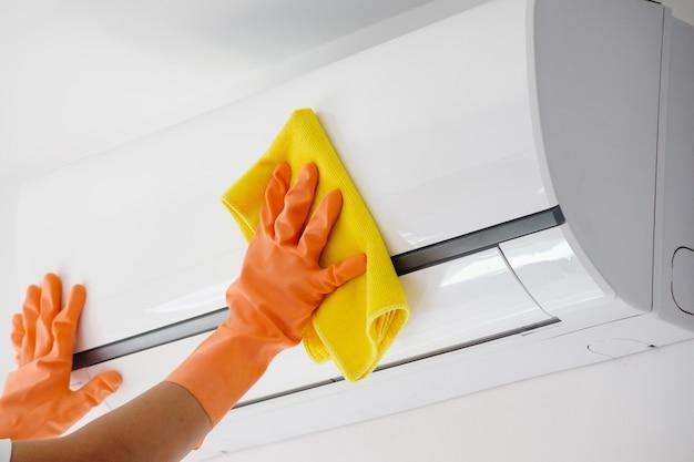 Uomo che pulisce il condizionatore d'aria con un panno in microfibra