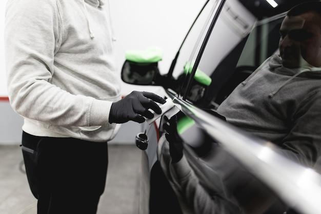 Un uomo che pulisce l'auto, i dettagli dell'auto (o il concetto di valeting). messa a fuoco selettiva.