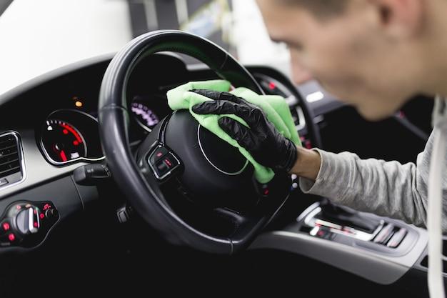 Un uomo che pulisce gli interni dell'auto, i dettagli dell'auto (o il concetto di valeting). messa a fuoco selettiva.