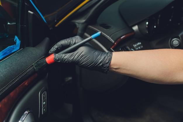 Un uomo che pulisce la macchina con un panno e una spazzola. dettagli dell'auto.