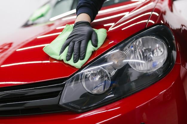 Un uomo che pulisce l'auto con un panno, un concetto di dettagli auto (o valeting). messa a fuoco selettiva.