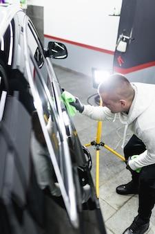 Un uomo che pulisce l'auto con un panno in microfibra, il concetto di dettagli dell'auto (o valeting). messa a fuoco selettiva.