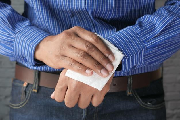 Mani di pulizia dell'uomo con la salvietta bagnata antisettica.