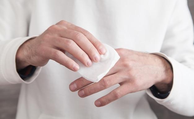 Uomo che pulisce la sua mano con un panno umido.